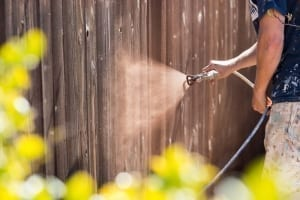 spraying a fence with stain